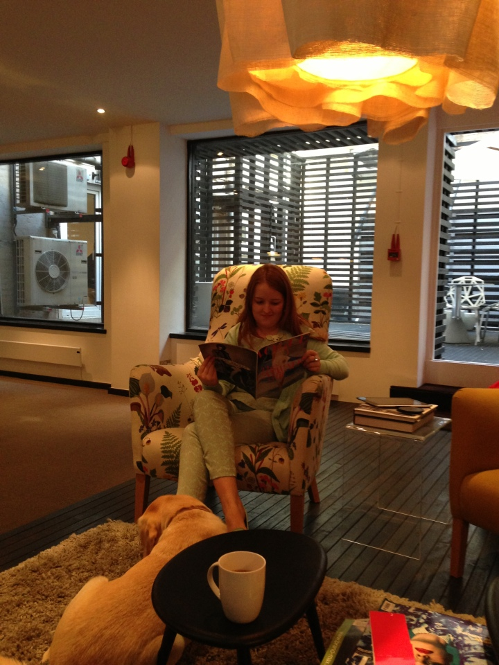 Image of me sitting on an armchair at the recording studio at Sohoo reading a Vogue