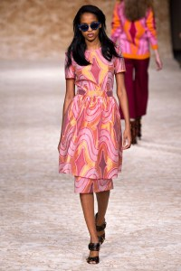 Image of a catwalk model wearing a 50's style dress in a vibrant pink and orange colours