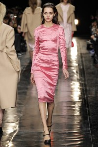 Image of a catwalk model in a salmon pink pencil dress