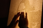 Image of the outline of hands tracing the tactile image of Mona Lisa