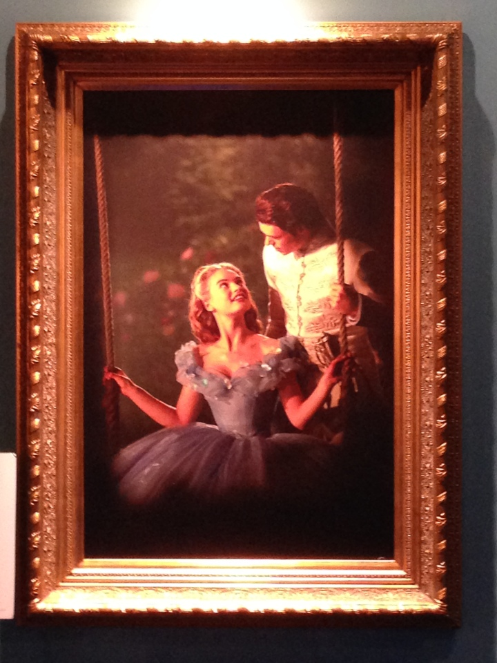 Image of a painting from the film depicting Cinderella sitting on a swing with the prince behind her