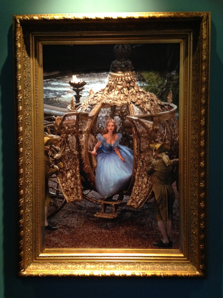 Image of a painting of a scene from the Cinderella film depicting Cinderella getting out of the golden coach.
