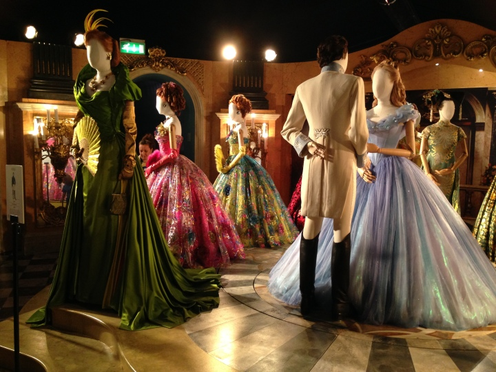 Image of the different ballroom costumes from the film including from left to right The Stepmother, stepsisters, the Prince and Cinderella