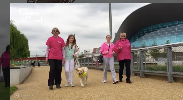 An image taken from the feature of me walking with one of the guides along with Chloe another long cane user with her guide